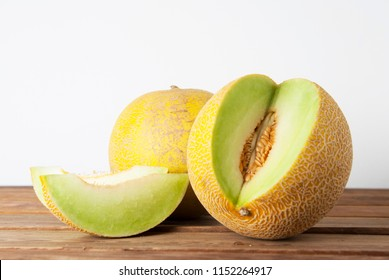 Cantaloupe yellow fresh melon isolated with sliced melon, wooden table, gray background. Summer fruits. Isolated.