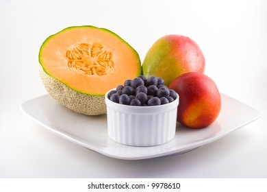 Cantaloupe,blueberries,mango and a nectarine share space on a white plate.