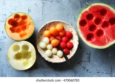 Cantaloupe,honeydew and watermelon balls on a plate with fresh melon in background