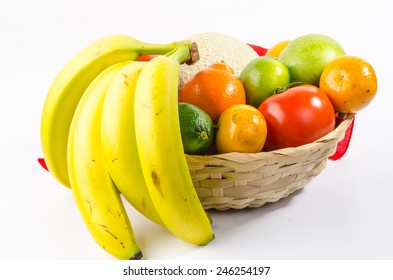Canteloupe, lime; orange, tomato, apple, tangerine, tangelo, bananas in basket against white background.