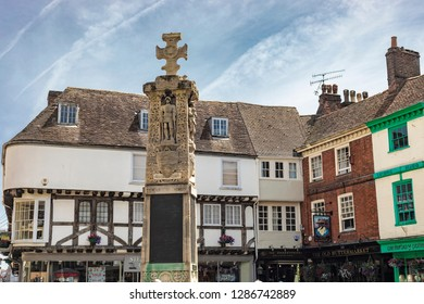 Canterbury, England - June 24, 2018: View the iconic Canterbury War Memorial sculpture in the middle of a street surrounded by pubs and shops in Kent, United Kingdom.