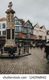 CANTERBURY, ENGLAND - October 28th, 2018: Canterbury War Memorial monolith in the village of Canterbury, with visitors walking around and classic english architecture around the square, Kent, England.