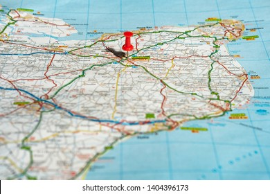 Canterbury, Kent, UK - Circa May 2019: Shallow focus of a red push pin located at this historic English city in the south east. Part of the english channel and Thames estuary are visible on the map.