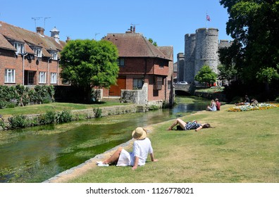 CANTERBURY, KENT, UK - JUNE 30, 2018. The Great Stour, riverside houses and the 14th century West Gate stone towers beyond at Canterbury in the English county of Kent, UK.
