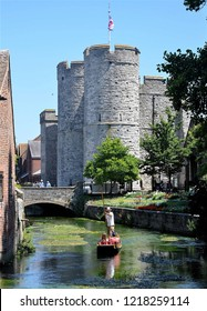 CANTERBURY, KENT, UK - JUNE 30, 2018. Punting on the River Stour towards the 14th century West Gate stone towers at Canterbury in Kent, England, UK.