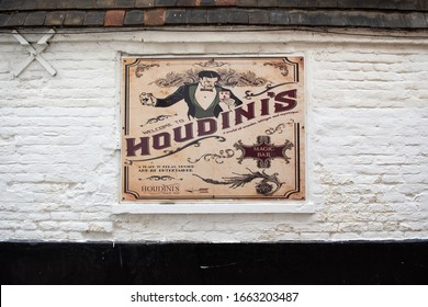 Canterbury, Kent/UK - February 22 2020: Advertising boards for Houdini's magic bar on St Peter's Street. One sign is mostly cream, the other colourful. Both feature Houdini. Set against white bricks.