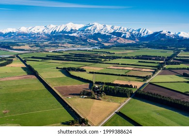 Canterbury Plain And The Southern Alps. An elevated view of the farmlands of the Canterbury Plain, on New Zealand's South Island, stretching away towards the mighty Southern Alps.