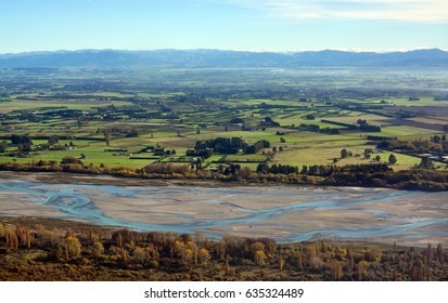 Canterbury Plains and Waimakariri River aerial view as the mist clears on an Autumn morning, New Zealand. In the background are the Southern Alps.