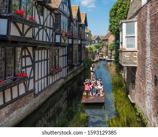 CANTERBURY, UK, - JULY, 11, 2019: Tourists enjoy a punt ride on the River Stour as they pass the 16th Century Old Weavers House in Canterbury, Kent, UK.