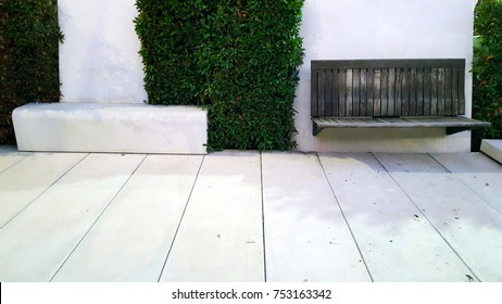 Cantilevered wooden slatted bench sticking out of a white concrete wall on a sunken garden with hedges and blocks.