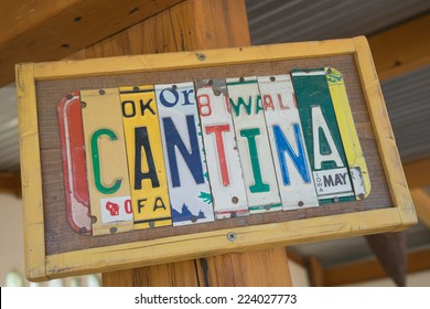 Cantina sign made out of state license plates on a wood frame in diagonal perspective