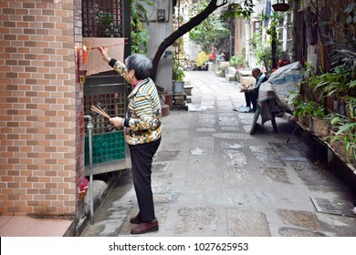 CANTON, CHINA – CIRCA FEBRUARY 2018: An old woman offers a sacrifice to the Heavenly official.  Burning incenses in front of the sacrificial altar.