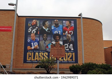 Canton OH: USA: Mar 31, 2021 – Mural of Class of 2021 inductees on outside of NFL Hall of Fame building. Historical Marker sign notes Cradle of Professional Football.