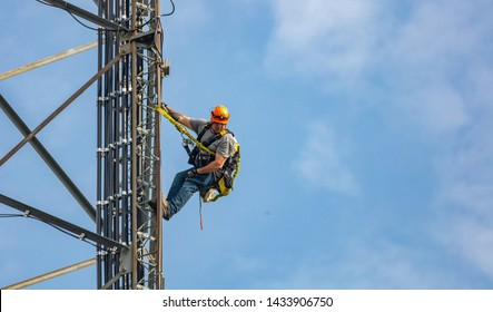 Canton, Ohio lake, USA. May 8, 2019. Communication maintenance. Technician climbing on telecom tower antenna against blue sky background, copy space