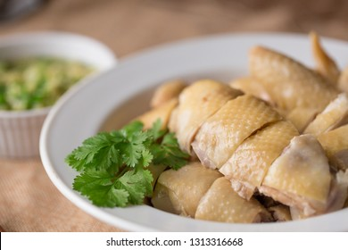Cantonese style Poached Chicken, White cut chicken, cut, with ginger and spring onion sauce at the background