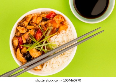 Cantonese Style Sweet And Sour Chicken With Rice Against A Green Background