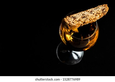 Cantuccini. Italian Cantucci Biscuit And A Glass Of Wine. Vin Santo. Black background. shining wine