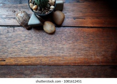 Cantus and stone on wooden table. texture and background concept