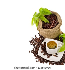 canvas bag with coffee beans decorated with green leaves and a cup of black coffee isolated on white background