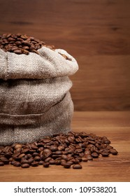 Canvas bag with coffee beans on rustic table with wooden texture