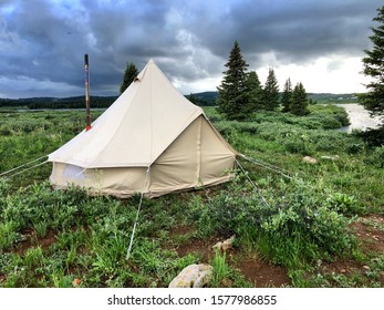 Canvas Bell tent set up lakeside with storm clouds in the background