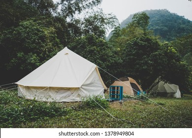 canvas bell tents outdoors at forest. Glamping at forest. Tourist camp with lots of tents in the woods