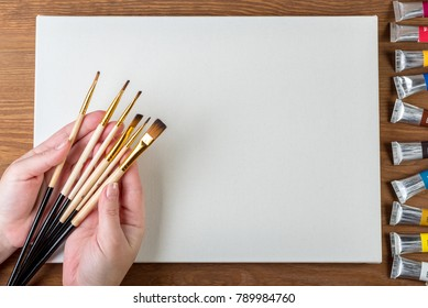 Canvas, brushes and paints on the table