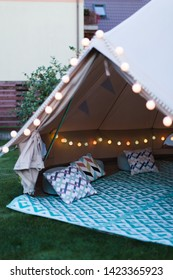Canvas cotton Bell tent in the yard decorated for summer kids party, vertical shot, pillows, garland, rug showwing
