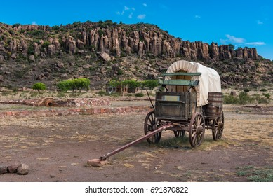 Canvas covered wagon with barrel on the side and green buck board and sunlight mountains in the background
