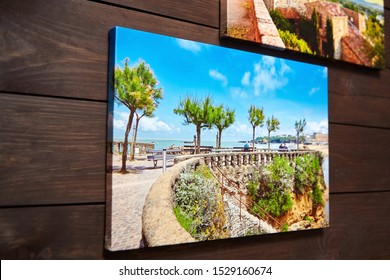 Canvas photo print on brown wooden background. Sample of gallery wrapping method. Side view of colorful photography hanging on a wall