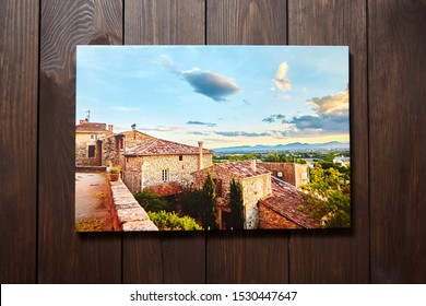 Canvas photo print on brown wooden background. Front view of colorful photography printed on glossy synthetic canvas. Photo hanging on a wall