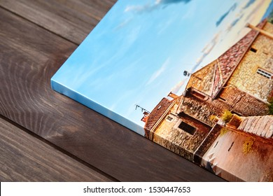 Canvas photo print on brown wooden background. Side view of colorful photography with gallery wrap. Photo printed on glossy canvas closeup