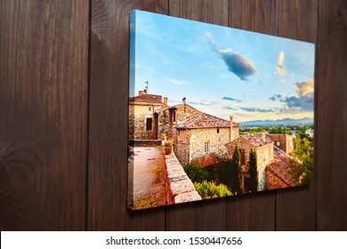 Canvas photo print on brown wooden background. Sample of gallery wrapping method of canvas stretching on stretcher bar. Side view of colorful photography hanging on a wall