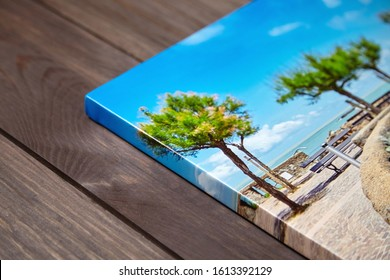 Canvas photo print on brown wooden background. Sample of gallery wrapping method of canvas stretching on stretcher bar. Corner and edge of colorful photography closeup
