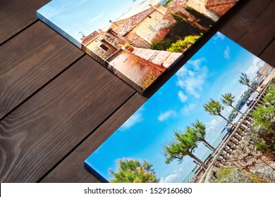 Canvas photo prints lying on a wooden table. Sample of gallery wrapping method of canvas stretching on stretcher bar. Side view of colorful photographs printed on glossy synthetic canvas