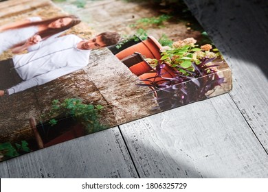 Canvas print with gallery wrap on wooden surface with sunlight and shadows. Sample of stretched wedding photography, side view.