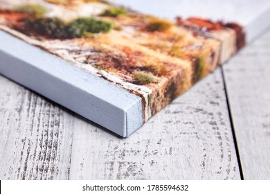 Canvas print on wooden background. Wrapped canvas, edge, corner, closeup. Detail of stretched landscape photography with gallery wrapping. Photo printed on canvas - Shutterstock ID 1785594632