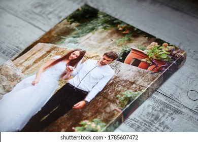 Canvas print. Photo printed on canvas. Sample of stretched wedding photography with gallery wrap, side view, closeup. Portrait on grey wooden surface - Shutterstock ID 1785607472