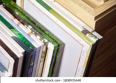 Canvas prints, stack of colorful photos with gallery wrapping method of canvas stretching on wooden stretcher bars. Samples of stretched photo canvases. Staple mount, back view