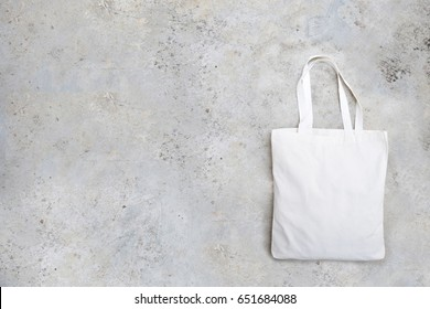 A canvas tote bag on cement background.
