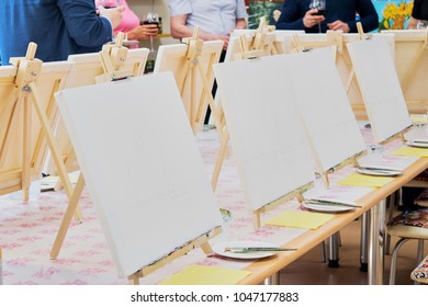 Canvases, brushes, palettes on the long wooden table ready for a masterclass in the art studio, people waiting to start drawing
