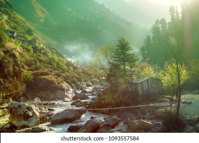 Canyon of mountain river and clachan (village) on steep slopes. Misty canyon photographed on sunny day, flashy river. Foothills Of Himalayas. India