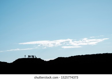 KING'S CANYON, NT/AUSTRALIA - APRIL, 2018. Silhouette of bush walkers standing on top of the canyon's edge.
