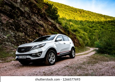 Canyon Temska, Serbia - 09.21.2018 / SUV car Kia Sportage 2.0 CRDI awd or 4x4, in the canyon next to a large rock, on a dusty road.