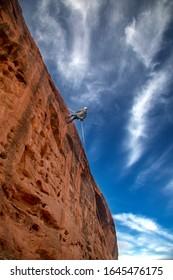 A canyoneer rappells down a sandstone cliff near St. George, Utah