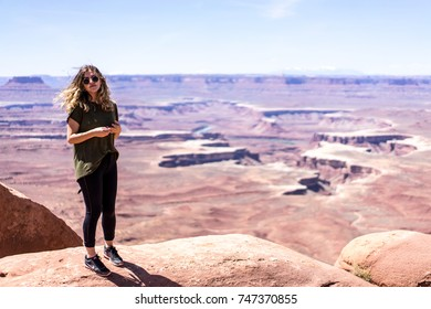 CANYONLANDS NATIONAL PARK, UTAH - MARCH 2016 - A woman stands in front of a view at Island in the Sky in Canyonlands National Park, Utah.