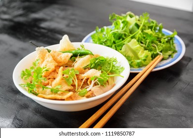 Cao Lau on black wooden table of street cafe at Hoi An (Hoian) in Quang Nam Province of central Vietnam. Cao Lau is a regional Vietnamese dish made with noodles, pork and local greens.