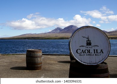 Caol Ila, Port Askaig, Islay, Scotland - May 11 2019: The view from the Caol Ila distillery pier onto the Paps of Jura with a Caol Ila barrel in front of the picture