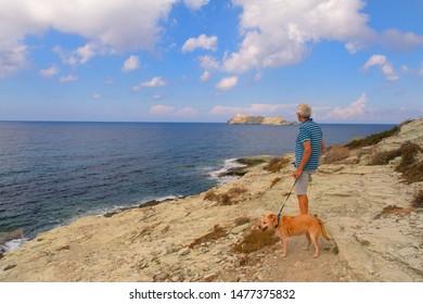 Cap corse man with dog standing at the coast