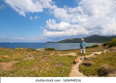 Cap corse man with dog walking at the coast